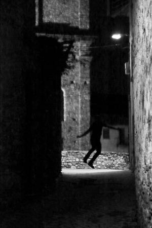 A man, one in shadowy, shadowy form between old walls of a dark alley Foto de archivo - 105971634