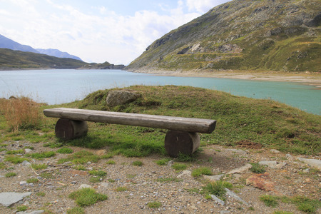 Wooden bench, bench at the reservoir Monte Spluga, at the Spluegen Pass, and surrounding mountains in summer Imagens