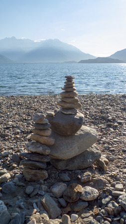 Pebbles stacked on top of each other on a small tower, layered, on the beach of Dongo, Gravedona on Lake Como