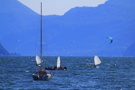 Surfer and yachtsman in the upper part of Lake Como in Italy