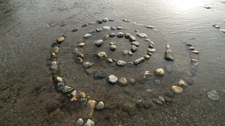 Spiral from pebbles to stones, on the shore, beach of Gravedona in Lake Como