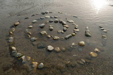 Spiral from pebbles to stones, on the shore, beach of Gravedona in Lake Como Stock fotó - 120804647