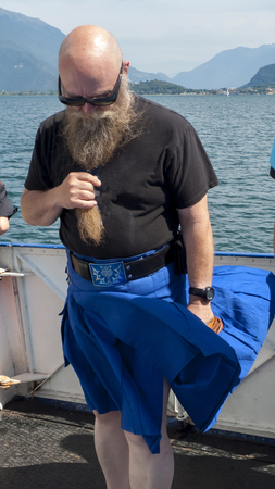 Man with long beard and sunglasses carries a kilt, Scot's skirt which flutters in the wind Stock Photo