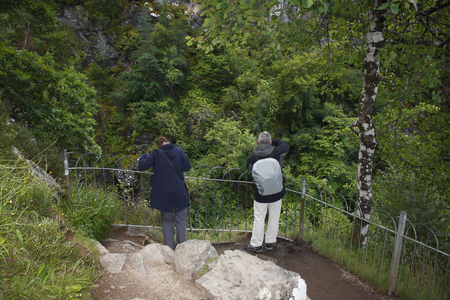 A man and a woman standing in the vantage point of the waterfall Fall of Foyers in Scotland