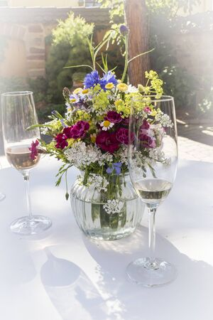 Champagne glasses festively arranged on a table with a bouquet of flowers