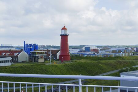 Red lighthouse in the harbor basin of Ijmuiden near Amsterdam