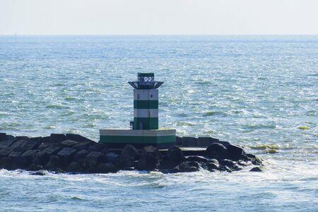 Green white lighthouse in the harbor basin of Ijmuiden near Amsterdam