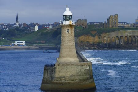 Tynemouth lighthouse in Great Britain, port entrance to Newcastle, with Tyne Castle in the background Stock Photo