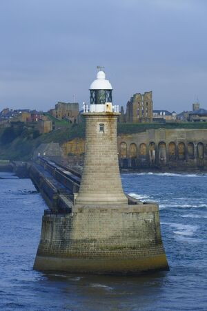 Tynemouth lighthouse in Great Britain, port entrance to Newcastle, with Tyne Castle in the background Standard-Bild
