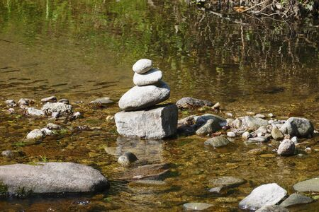 Stones stacked on top of each other in a stream bed, esoteric exercise