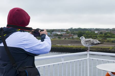 A man photographs a fearless, cheeky seagull, in background Newcastle upon Tyne