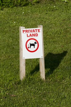 Tip sign on the lawn, with the English label PRIVATE LAND
