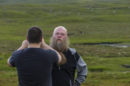 A man film takes a photo of a man with long beard and glasses Фото со стока