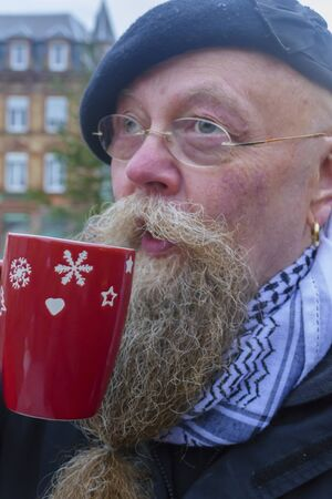 Man with long beard and glasses, drinks a cup of mulled wine Reklamní fotografie