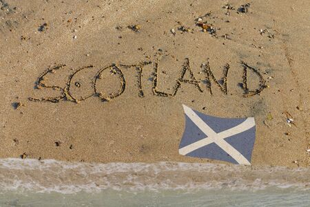 English word Scotland written in sand with Scottish flag, symbol for brexit referendum