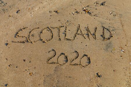 English word Scotland 2020 written in sand, symbol for Brexit