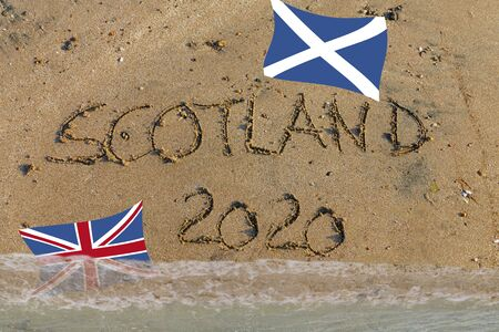 English word Scotland 2020 written in sand with Scottish flag and Union Jack, Symbol for Brexit Referendum