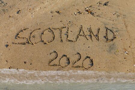 English word Scotland and 2020 written in sand, symbol for brexit referendum