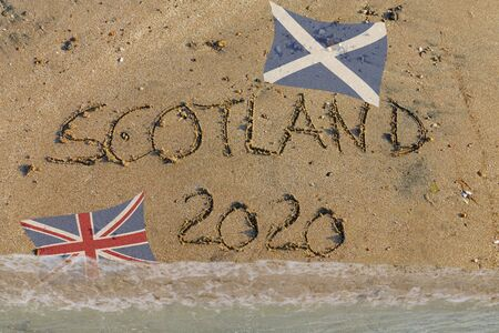 English word Scotland 2020 written in sand with Scottish flag and Union Jack, symbol for brexit referendum Reklamní fotografie