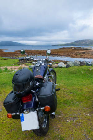Motorcycle stands on the coast of Loch Eisort, Ord, Isle of Skye, overlooking the Guillin Mountains