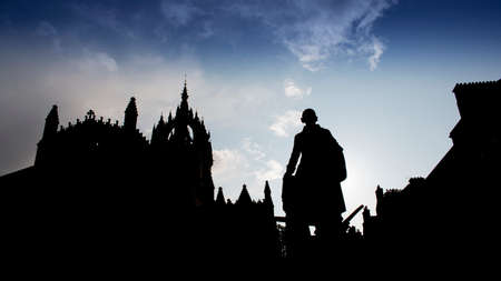 Silhouette of Adam Smith statue, with St. Giles Cathedral under blue sky 免版税图像