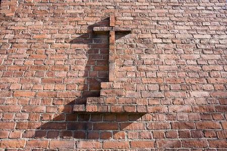 worship service: Christian cross on red brick wall
