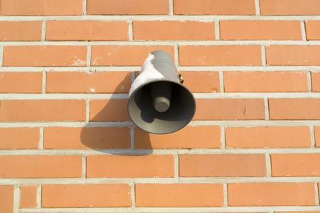 public address: loudspeaker on red brick wall