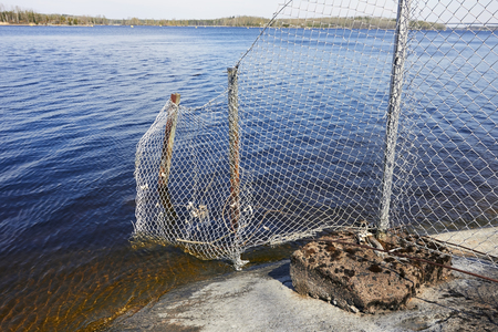 wire netting fence on rocky shore