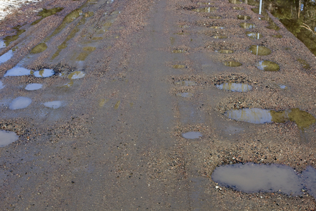 wet dirt road with puddles in spring, Finland