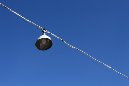 Old sport field lamp against blue sky background