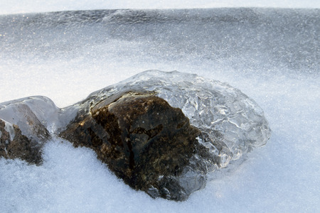 ice covered stone on lake shore, Finland Stock Photo
