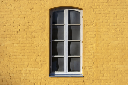 window on yellow painted brick wall