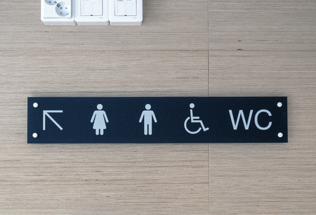 Toilet sign and direction on wall Stock Photo