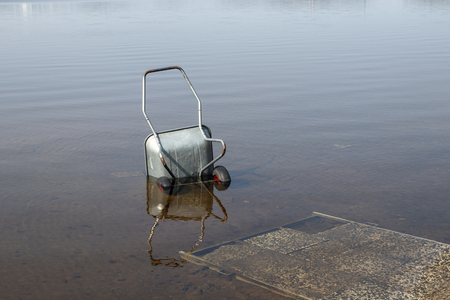 wheelbarrow lying in a lake, Finland Stock Photo