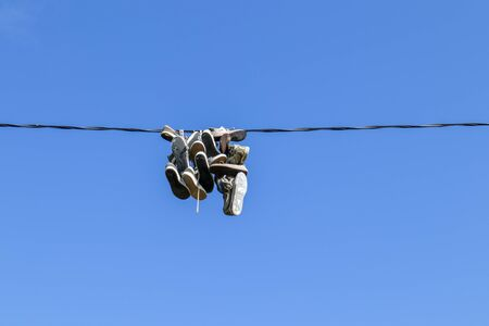shoes hanging from a electric wire Imagens - 131843710