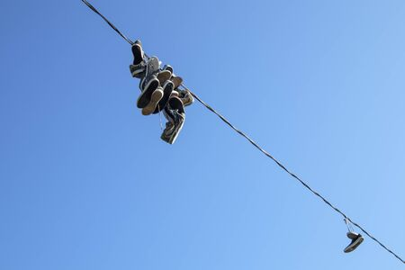 shoes hanging from a electric wire Imagens - 131801785