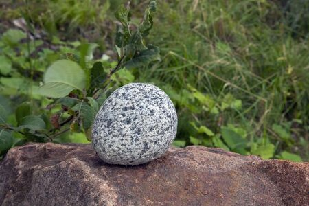 Round gray stone on top of brown boulder outdoors