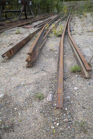 dismantled railroad rails on ground outdoors Stock Photo