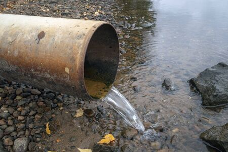 water running out of drain pipe into lake, Finland Imagens - 133228780