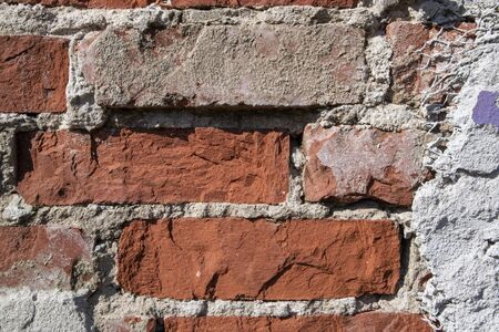 red brick wall detail with damaged plaster Standard-Bild