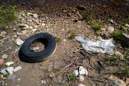 car tyre and piece of plastic on shore
