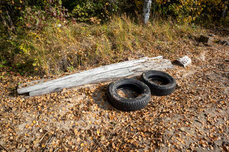 two dumped car tyres outdoors