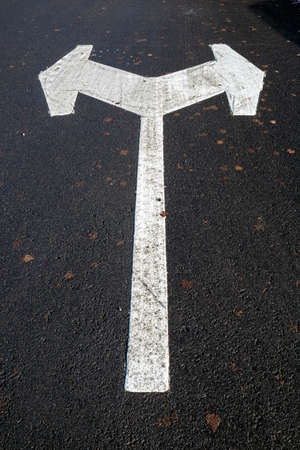white directional arrow in parking lot