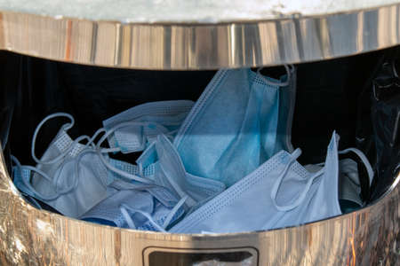 used coronavirus respiratory infection protection masks in the dust bin