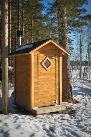 A wooden outhouse toilet in springtime
