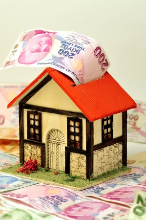 Miniature house over money isolated photo