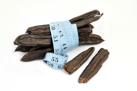attenuation: carob and measure on white background Stock Photo