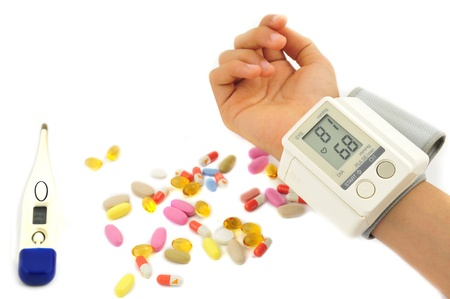 blood pressure and pills in white background photo