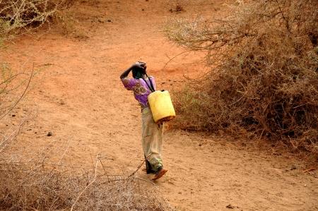 Mujer africana llevando latas de agua