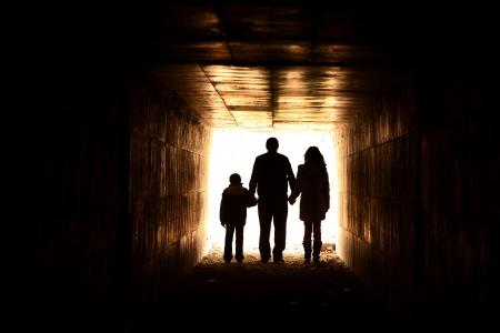 トンネル: 後ろに照明家族のシルエット